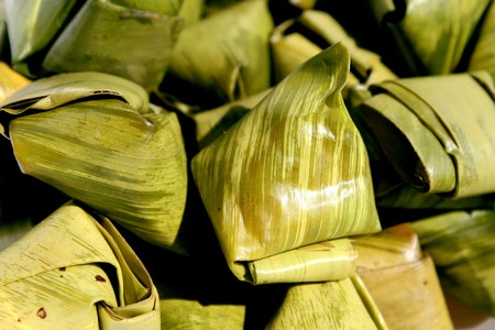 stuffed dough pyramid dessert made from sticky rice flour and palm sugar wrapped with banana leaf in pyramid shape photo