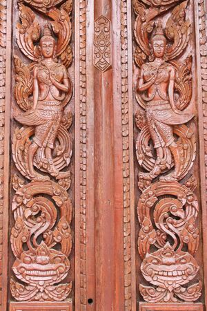 Thai art carving and painting on wooden window of temple photo