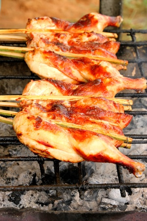 Grilled chicken over gridiron and low heat from natural charcoal Stock Photo