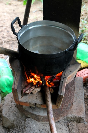 Traditional Thai boiling or steaming food in pot over an old stove photo