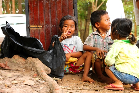 SIEMREAP, KHMER REPUBLIC - NOVEMBER 6 : The unidentified group of Khmer children are begging for money from the tourist in Angkor Thom, one of Khmer ancient sanctuaries and one of them shows a thank you sign on November 6, 2011 at Angkor Thom, Siemreap, K