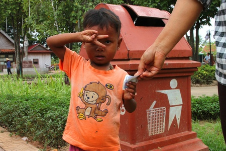 SIEMREAP, KHMER REPUBLIC - NOVEMBER 7 : The unidentified Khmer boy is given some money and showing thank you sign in city public park on November 7, 2011 at Siemreap, Khmer Republic.