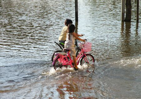 KOSUMPHISAI, MAHASARAKHAM, THAILAND - OCTOBER, 27 : An unidentified girls are riding bicycles in local road in trouble due to heavy monsoon rains have been drenching Thailand since mid-July, causing widespread flooding in Kosumphisai, with rising water an