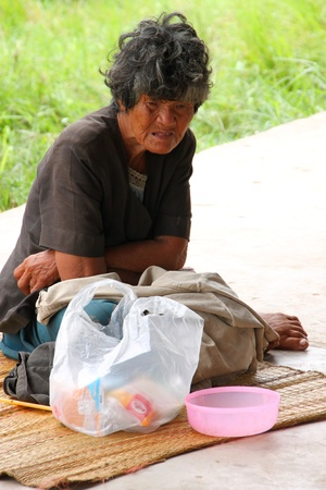 BORABUE, MAHASARAKAM, THAILAND - AUGUST 1 : An unidentified homeless woman is sitting on the floor and waiting for some help from the people that passing by on August 1, 2011 at Borabue, Mahasarakam, Thailand.