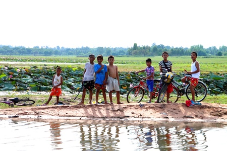 BORABUE, MAHASARAKAM, THAILAND - MAY 31 : The unidentified group of rural Thai young boys are standing and acting to camera near their wetland in happiness mood on May 31, 2011 at Borabue,  Mahasarakam, Thailand. Stock Photo - 11259989