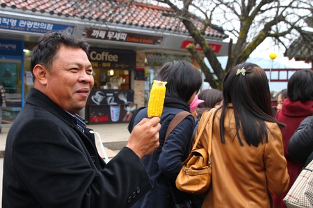 NAMINARA REPUBLIC, KOREA - NOVEMBER 26 : The unidentified tourist man is eating boiled corn at ferry port on November 26, 2011 at Naminara Republic, Korea.
