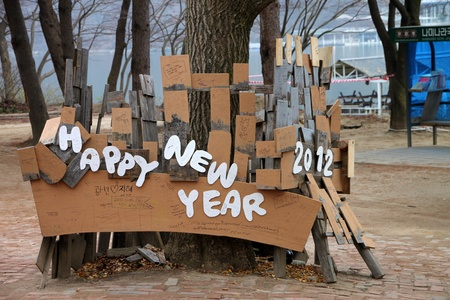 republic of korea: NAMINARA REPUBLIC, KOREA - NOVEMBER 26 : The happy new year 2012 wooden sign is locating for welcome the tourists on November 26, 2011 at Nami island, Naminara Republic, Korea. Editorial