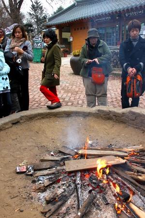 NAMINARA REPUBLIC, KOREA - NOVEMBER 26 : The unidentified group of tourists are standing around fireplace on November 26, 2011 at Nami island, Naminara Republic, Korea.