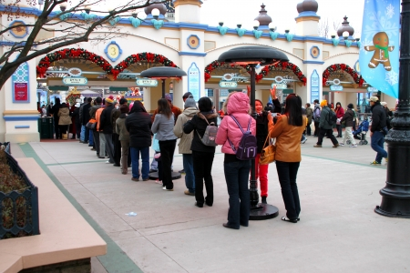 EVERLAND, YONGIN, KOREA - NOVEMBER 26 : The unidentified group of tourists are queuing and be happy at the entrance way on November 26, 2011 at Everland, Yongin, Korea.