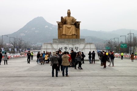 CENTRAL SEOUL, KOREA - NOVEMBER 27 : The unidentified tourists are enjoy travelling and be happy in front of King Sejong statue and Seoul city hall on November 27, 2011 at Central Seoul, Korea.