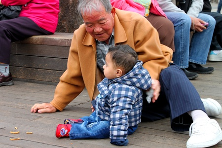 CENTRAL SEOUL, KOREA - NOVEMBER 27 : The unidentified boy and old man are playing together on wooden floor on November 27, 2011 at Namsan Seoul Tower, Central Seoul, Korea.