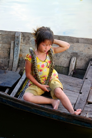 SIEMREAP, KHMER REPUBLIC - NOVEMBER 5 : The unidentified Khmer girl is sitting on boat and playing with  python show to the tourists on November 5, 2011 at Tonle Sap Lake, Siemreap, Khmer Republic.