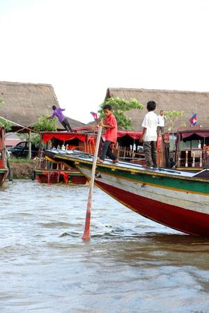 SIEMREAP, KHMER REPUBLIC - NOVEMBER 5 : The unidentified Khmer boy is controling travel boat on November 5, 2011 at Tonle Sap Lake, Siemreap, Khmer Republic. Stock Photo - 11542747