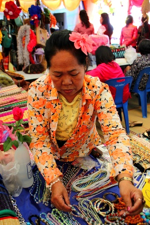 PAYAKKAPHUMPHISAI, MAHASARAKHAM - DECEMBER 17 : The unidentified woman is selling One Tambol One Product (OTOP) in festival season on December 17, 2011 at district hall plaza, Payakkaphumphisai, Mahasarakham.