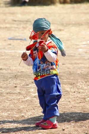 HUAI RAT, BURIRAM - DECEMBER 18 : The unidentified Thai young boy is playing little wind turbine in kites festival season on December 18, 2011 at sport ground, Huai Rat, Buriram.