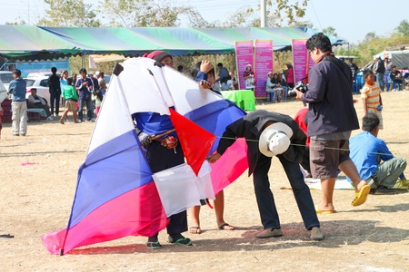 HUAI RAT, BURIRAM - DECEMBER 18 : The unidentified Thai men are preparing their kite to contest in kites festival season on December 18, 2011 at sport ground, Huai Rat, Buriram. Stock Photo - 11565636