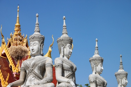 Buddha statues in adorned style on roof of temple photo