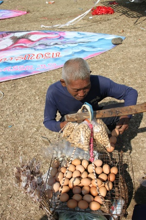 HUAI RAT, BURIRAM - DECEMBER 18 : The unidentified Thai man is buying grilled egg in northeast kites festival season on December 18, 2011 at sport ground, Huai Rat, Buriram.