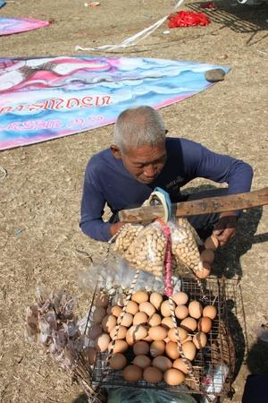 HUAI RAT, BURIRAM - DECEMBER 18 : The unidentified Thai man is buying grilled egg in northeast kites festival season on December 18, 2011 at sport ground, Huai Rat, Buriram.