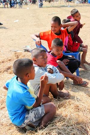 HUAI RAT, BURIRAM - DECEMBER 18 : The unidentified Thai children are seeing kites show in northeast kites festival season on December 18, 2011 at sport ground, Huai Rat, Buriram.