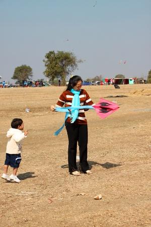 HUAI RAT, BURIRAM - DECEMBER 18 : The unidentified Thai woman is playing kite in northeast kites festival season on December 18, 2011 at sport ground, Huai Rat, Buriram.