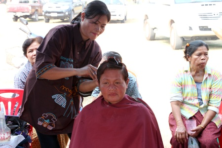 BORABUE, MAHASARAKHAM, THAILAND - JANUARY 19 : The unidentified woman is making haircut on January 19, 2012 at Wat Dong Keng, Borabue, Mahasarakham, Thailand.