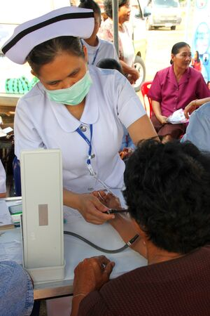 BORABUE, MAHASARAKHAM, THAILAND - JANUARY 19 : The unidentified nurse is measuring a patient blood pressure on January 19, 2012 at Wat Dong Keng, Borabue, Mahasarakham, Thailand.