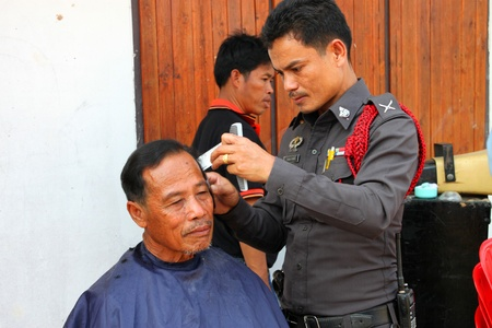 BORABUE, MAHASARAKHAM, THAILAND - JANUARY 19 : The unidentified policeman is making haircut on January 19, 2012 at Wat Dong Keng, Borabue, Mahasarakham, Thailand. Stock Photo - 12059443