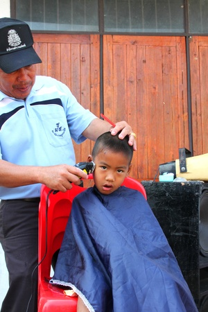 BORABUE, MAHASARAKHAM, THAILAND - JANUARY 19 : The unidentified policeman is making haircut on January 19, 2012 at Wat Dong Keng, Borabue, Mahasarakham, Thailand.