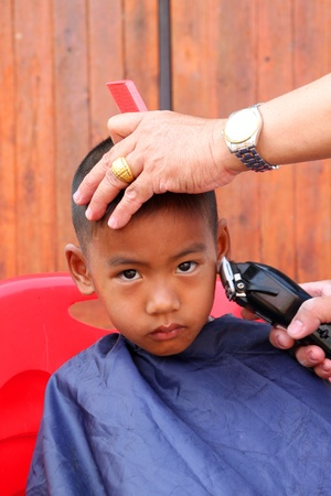BORABUE, MAHASARAKHAM, THAILAND - JANUARY 19 : The unidentified boy has a haircut service on January 19, 2012 at Wat Dong Keng, Borabue, Mahasarakham, Thailand.