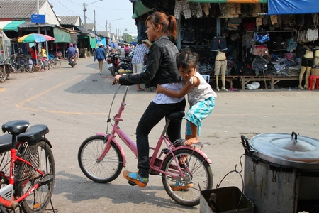 SAKAEO, THAILAND - FEBRUARY 3 : The unidentified Khmer woman is riding a bicycle on February 3, 2012 at Rong Kluea Market, Sakaeo, Thailand.