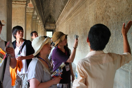 handscraft: SIEMREAP, KHMER REPUBLIC - FEBRUARY 11 : The unidentified tourists are looking at carvings on wall on February 11, 2012 at Angkor Wat, Siemreap, Khmer Republic.