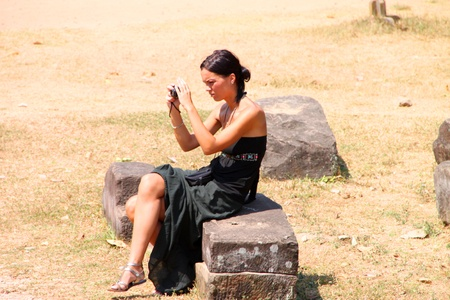 SIEMREAP, KHMER REPUBLIC - FEBRUARY 11 : The unidentified tourist is relaxing and checking photos of ancient architecture on February 11, 2012 at Angkor Thom, Siemreap, Khmer Republic. Stock Photo - 12272703