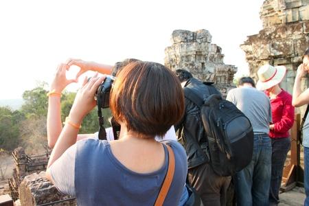 indo china: SIEMREAP, KHMER REPUBLIC - FEBRUARY 11 : The unidentified tourist is taking a photograph on February 11, 2012 at Phnom Bakheng mountain, Siemreap, Khmer Republic.