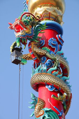 Colorful dragons on red post in front of chinese shrine photo