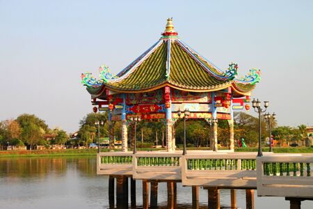 Chinese style pavilion in middle of pond photo