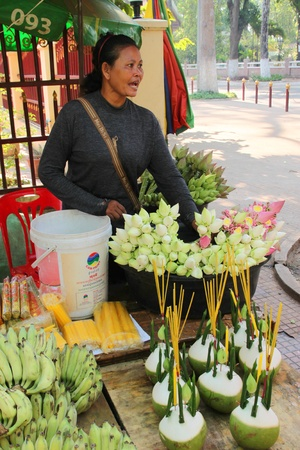 indo china: SIEMREAP, KHMER REPUBLIC - FEBRUARY 12 : The unidentified woman is selling religious offerings and flowers on February 12, 2012 at City Pillar, Siemreap, Khmer Republic.