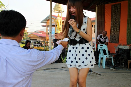 BORABUE, MAHASARAKHAM, THAILAND - FEBRUARY 9 : The unidentified singer is performing and taking money reward in grand opening OTOP market on February 9, 2012 at Borabue city hall plaza, Mahasarakham, Thailand.