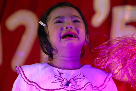 PAYAKKAPHUMPHISAI, MAHASARAKHAM, THAILAND - MARCH 11 : The unidentified pupil is crying while performing modern dance in the end of semester Iam Suk school party on March 11, 2012 at city hall plaza, Payakkaphumphisai, Mahasarakham, Thailand.