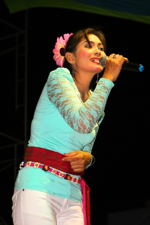 NACHAUK, MAHASARAKHAM, THAILAND - MARCH 17 : The unidentified woman is singing in song contest on March 17, 2012 at city hall plaza, Nachauk, Mahasarakham, Thailand. Stock Photo - 12690835