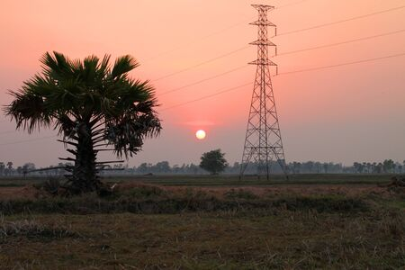 Very high voltage pole tower, rural field and sky at sunset photo