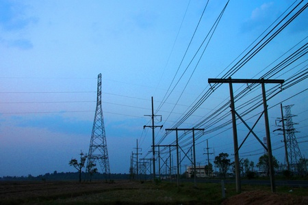 Very high voltage pole towers, rural field and sky after sunset photo