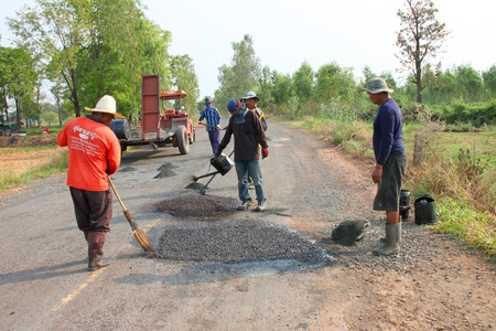 NACHAUK, MAHASARAKHAM, THAILAND - MARCH 19 : The unidentified workers are repairing local road on March 19, 2012 at Samrong - Porpan Way, Nachauk, Mahasarakham, Thailand.
