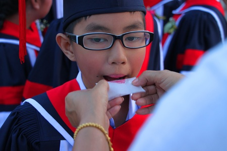 PAYAKKAPHUMPHISAI, MAHASARAKHAM, THAILAND - MARCH 11 : The unidentified boy is waiting for school graduation on March 11, 2012 at city hall plaza, Payakkaphumphisai, Mahasarakham, Thailand.