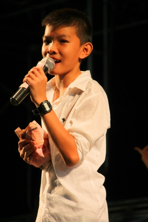 YANGSISURAT, MAHASARAKHAM, THAILAND - MARCH 23 : The unidentified boy is singing local song in Buarin In Concert on March 23, 2012 at Ban Nong Bua Santu, Yangsisurat, Mahasarakham, Thailand.
