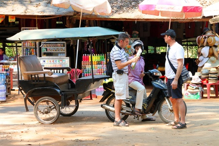 SIEMREAP, KHMER REPUBLIC - FEBRUARY 11 : The unidentified tourists are asking Khmer driver the way to ancient architecture on February 11, 2012 at Prasat Preah Khan, Siemreap, Khmer Republic.