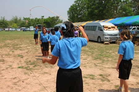 NACHUAK, MAHASARAKHAM, THAILAND - MARCH 21 : The unidentified children are skipping rope on March 21, 2012 at Nong Bua Daeng School playground, Nachuak, Mahasarakham, Thailand.