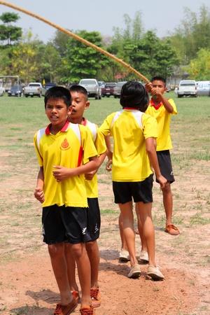 NACHUAK, MAHASARAKHAM, THAILAND - MARCH 21 : The unidentified children are skipping rope on March 21, 2012 at Nong Bua Daeng School playground, Nachuak, Mahasarakham, Thailand.