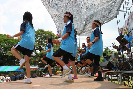 NACHUAK, MAHASARAKHAM, THAILAND - APRIL 13 : The unidentified women are performing aerobic dance in Songkran Day on April 13, 2012 at district hall plaza, Nachuak, Mahasarakham, Thailand. Stock Photo - 13154998