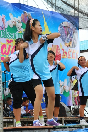 NACHUAK, MAHASARAKHAM, THAILAND - APRIL 13 : The unidentified women are performing aerobic dance in Songkran Day on April 13, 2012 at district hall plaza, Nachuak, Mahasarakham, Thailand. Stock Photo - 13154968